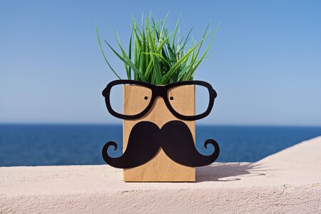 Funny face on paper bag with mustache and eyeglasses on blue sky background. November mens health cancer prostate awareness concept