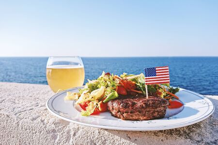Plate with grilled juiciest burger meat and vegetables decorated with USA flag and glass of beer, closeup view, outdoor party
