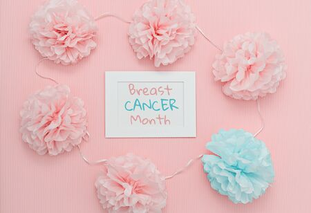 Text Breast cancer month in white frame with symbolic healthy and sick flower buds, symbolizing fight humanity against cancer. Breast cancer awareness month concept Фото со стока