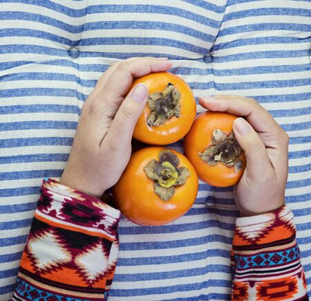 Female Hand holds three ripe persimmon on striped blue background. Minimal concept for decoration with copy space 스톡 콘텐츠