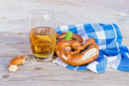 Traditional of german pretzel and glass of beer on wooden background. Salted pretzel is traditional German snack for beer and sausages. Oktoberfest Celebration concept