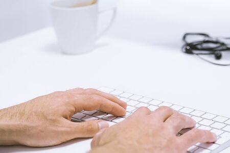 Mans hand typing working on wireless keyboard on white work place, closeup and above view. Light office workplace concept 스톡 콘텐츠