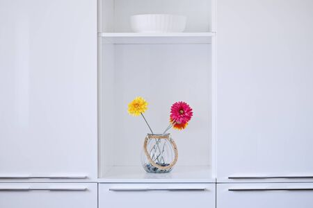 Minimalist white kitchen interior design with colorful flowers in vase. Glossy cupboard surface