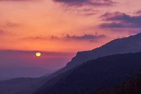 Scenic view of amazing pink-yellow sunset in Sicilian mountains with beautiful cloudscape