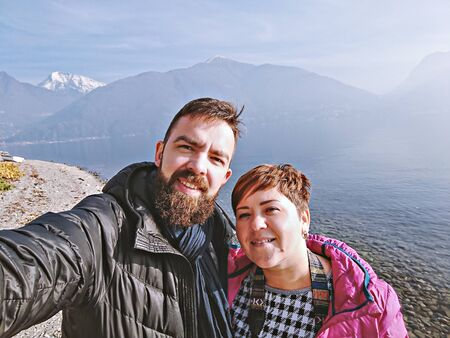 Smiling millennial couple taking selfie scenic Italian mountains against. Real people vacation lifestyle 스톡 콘텐츠