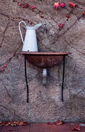 White vintage metal jug on ceramic sink in backyard in garden. Autumn in shabby chic style
