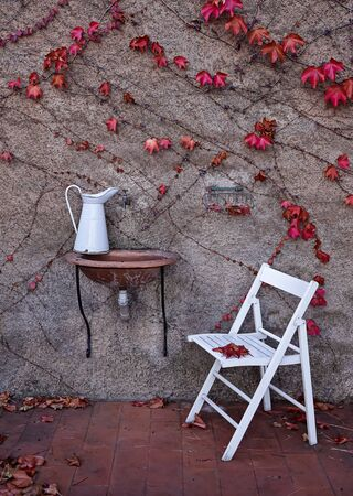 White vintage metal jug on ceramic sink and chair in backyard in garden. Autumn in shabby chic style