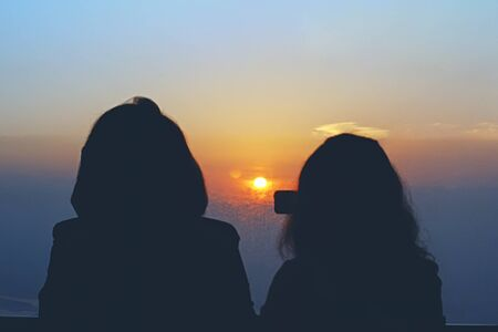 Silhouettes of two women looking at the sunrise on observation tower, selective focus