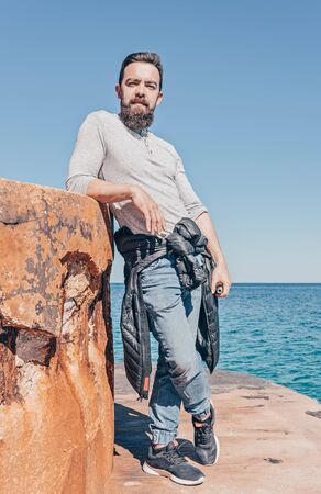 Portrait of bearded caucasian millennial man in casual clothes against seascape, outdoor, full-length real people portrait