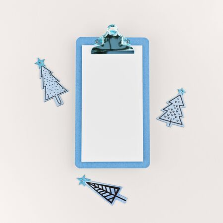 Blank on clipboard and wooden painted funny Christmas trees on white background. Happy New Year and Christmas greeting card mock up, minimalist flat lay style