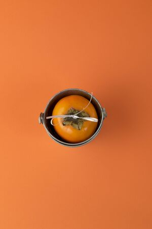 One ripe persimmon in basket on orange background. Minimal concept for decoration with copy space