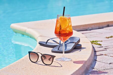 Wineglass of cold cocktail  near swimming pool with sunglasses. Traditional Italian summer Aperitif Cocktail concept