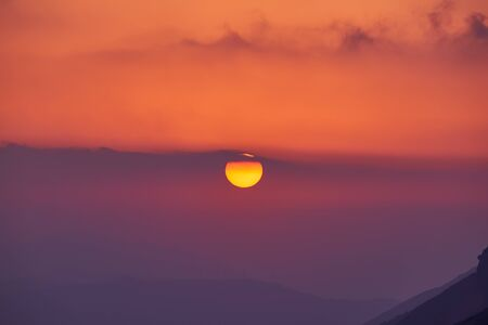 Landscape with wonderful golden sunset in mountains at sunset with big yellow sun disk. Scenic view of foggy hills covered by forest
