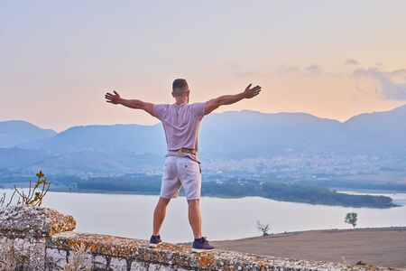 Rear view of man standing with raised hands and enjoying dusk with scenic view of lake and hills