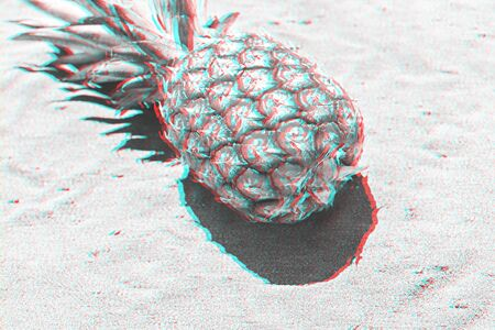Pineapple fruit on sandy beach with copy space and glitch effect. Summer background concept