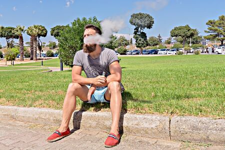 Bearded viper hipster sits on grass and enjoys weather in park