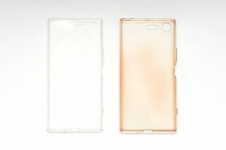 Silicone case on smartphone, damaged and brand new on white background, top view