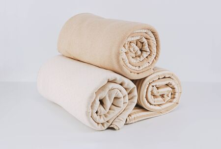 Closeup pile wrapped folded natural beige cotton blanket for kid on white background