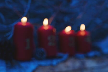 Defocused Four red advent candles with number as Catholic symbol of Christmas. Christmas decoration with candle for advent season four candles burning