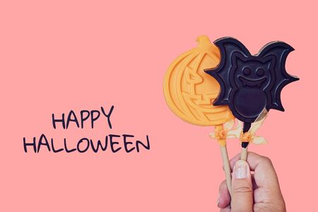 Chocolate lollipops in shape of pumpkin and bat. Pink pastel Halloween concept greeting card