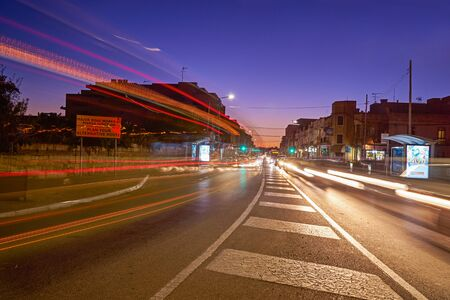 View of road with active road traffic at sunset, headlights by cars and slow-motion effect