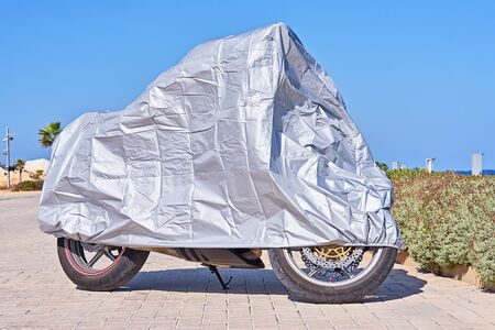 Waterproof cover for motorcycle with silver reflective surface protective. Motorbike covered with fabric shield parked at outdoor Reklamní fotografie