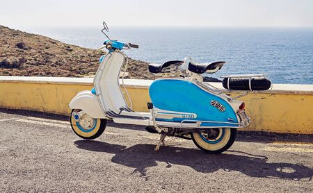 Vintage blue-white two-seater scooter parked on street near sea coastline: Zurrieg, Malta - July 9, 2016 Reklamní fotografie
