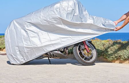 Biker covers motorcycle with waterproof cover with silver reflective surface protective. Motorbike covered with fabric shield parked at outdoor Reklamní fotografie