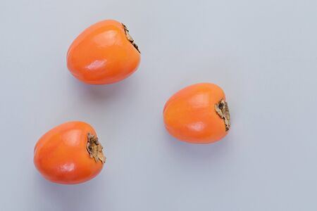 Three ripe persimmons on blue background. Concept of autumn seasonal fruits, flat lay top view, copy space