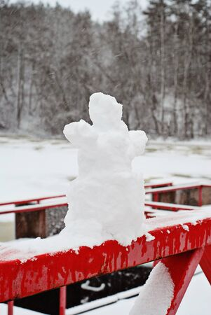 Miniature cute snowman made of natural snow on background of snowy park. Winter entertainment concept