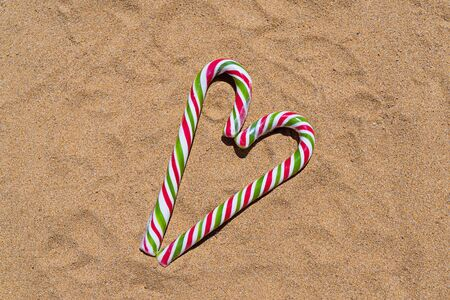 Christmas candy cane heart on sandy beach with copy space. Merry Christmas and Happy New Year at beach concept