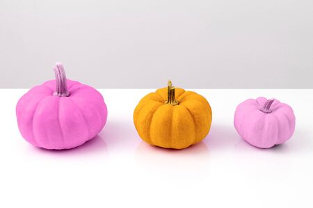 Three colored pumpkins stand in a row. Halloween interior decoration in modern kitsch style.