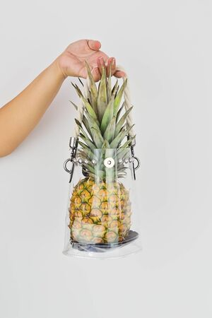 Womans hand holding fresh ripe pineapple in transparent plastic bag on white background. Reducing use of plastic in shopping and everyday life