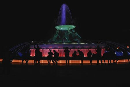 Silhouettes of people sitting near Triton fountain in the central square of valletta with night colorful illumination, abstract street urban scene