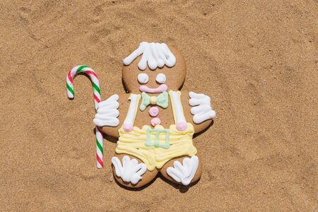 Gingerbread cookie men with candy cane on sandy beach. closeup flat lay. Merry Christmas and Happy New Year at beach concept