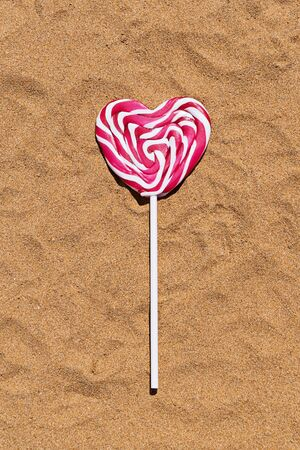 Closeup pink lollipop in heart shape on sand, falt lay view. Happy Valentines day concept Reklamní fotografie