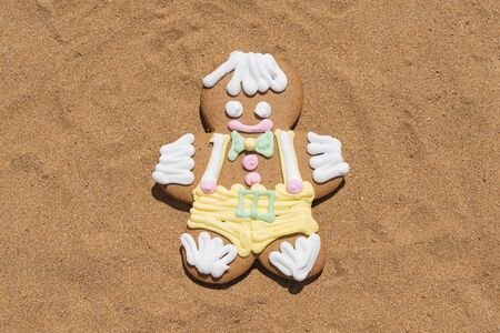 Smiling gingerbread cookie men on sandy beach, closeup flat lay. Merry Christmas and Happy New Year at beach concept