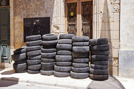 Pile of used car rubber tires near auto garage on street. Tyre fitting service Reklamní fotografie