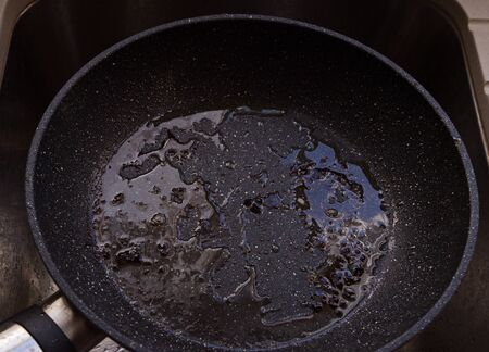 Closeup view of hot iron pan with non-stick surface and oil in the sink