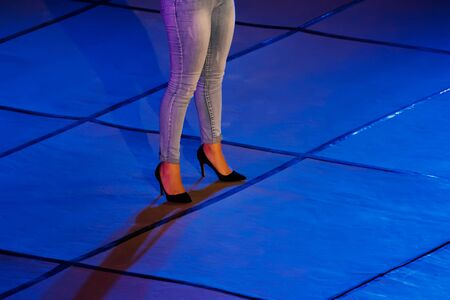 Womens legs in high heels on stage in the neon spotlight during concert, closeup view, copy space