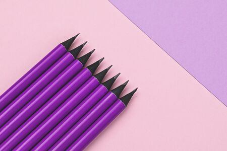 Purple pencils lie on colorful geometric background. Back to school concept. Copy space and duotone