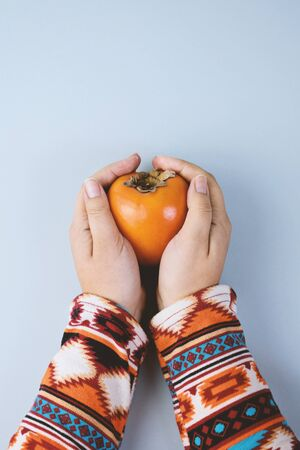 Female Hand sholds ripe persimmon on blue background. Minimal concept for decoration with copy space