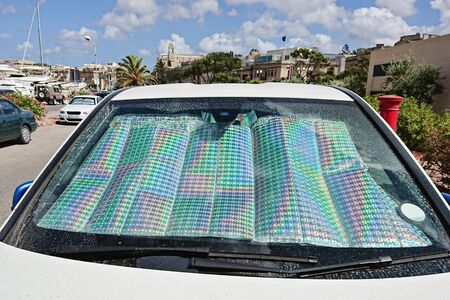 Windshield of car with protective reflective sunscreen surface inside car parked with sunbeams. Method for protecting heated by sun rays inside car Reklamní fotografie