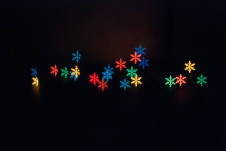 Beautiful abstract pattern with colorful snowflake on black background. Christmas decoration element. Seasonal holiday glow light effect Imagens