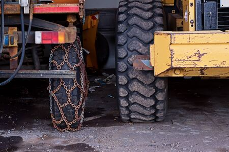 Closeup view of wheel of truck with rusty chains of safety on road. Road safety concept during road icing