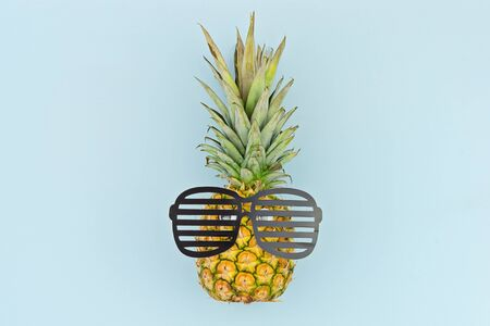 Funny face by pineapple with glasses on blue background. Back to school or sale school stationery concept template Reklamní fotografie