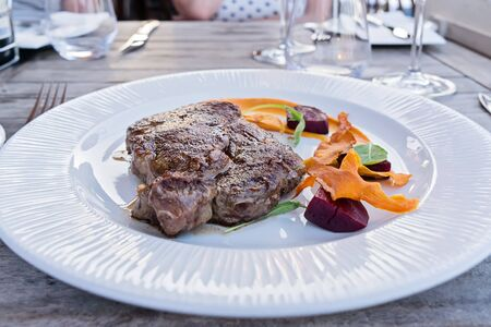 Cooked medium roasted fresh steak by angus beef with vegetables on white plate on table in restaurant, starter dish menu