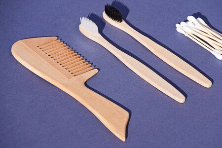 Set of wooden hairbrush, toothbrush and cotton buds made from renewable, biodegradable and recyclable material bamboo on blue background. Zero waste concept, selective focus Reklamní fotografie