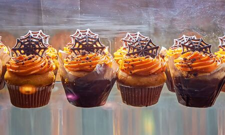Freshly baked muffins and cupcake decorated with skulls and ghosts for Halloween. Sweet Treats for Halloween Celebrations for kids