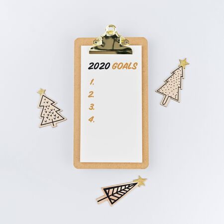 Goals 2020 on clipboard with wooden Christmas trees on white background. Holiday decorations and clipboard with wish list on white background, flat lay style. Planning and resolution concept